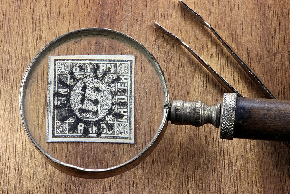 Image of a German stamp being viewed through a magnifying glass